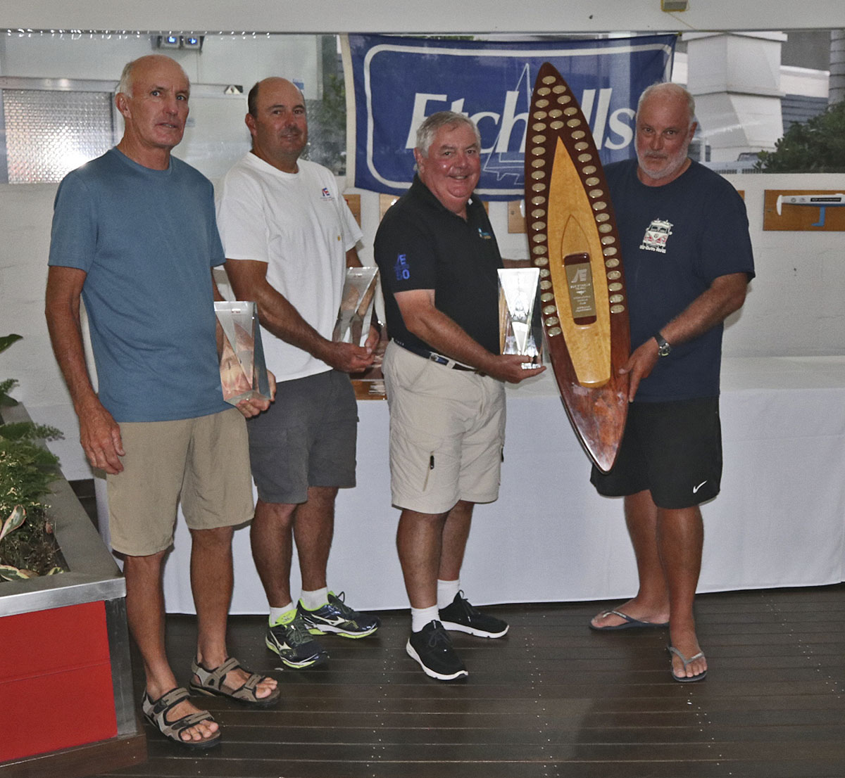 RQYS Commodore presents Iain Murray, Richie Allanson and Colin Beashel with their loot for winning the 2019 Etchells Australian Championship